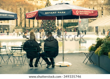 NEW YORK CITY - DECEMBER 4, 2015:  Vintage style View of couple sitting at Bryant Park Citi Pond in New York City with Christmas tree visible in the background during the holiday season - stock photo