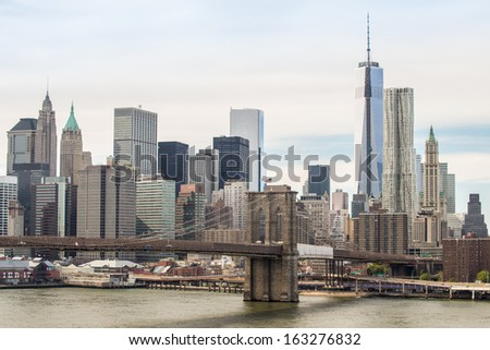 New York City downtown financial district skyline with Brooklyn Bridge on East River - stock photo