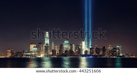 New York City downtown skyline at night panorama over Hudson River and September 11 tribute light - stock photo