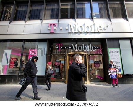 NEW YORK CITY - FEB. 25, 2015:  Pedestrians walk past a T-Mobile retail store. T-Mobile International AG is a holding company for Deutsche Telekom AG's  communications subsidiaries outside Germany.   - stock photo