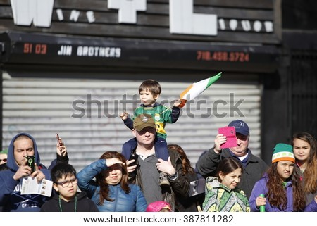 NEW YORK CITY - FEBRUARY 6 2016: Mayor Bill de Blasio and members of the NYC city council marched in Sunnyside's annual St. Pat's For All parade. Little boy rides dad's shoulders with Irish flag - stock photo