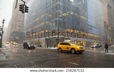 NEW YORK CITY - FEBRUARY 21, 2015:  Snow falling on wet winter day in midtown Manhattan as taxi goes by intersection.  - stock photo