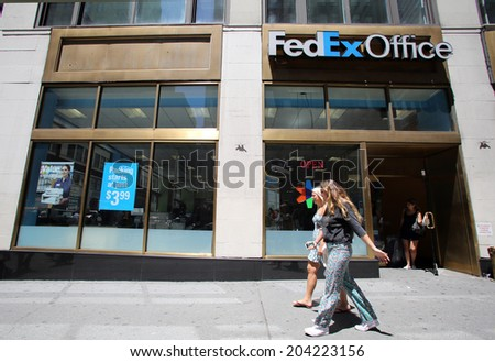 NEW YORK CITY - FRIDAY, JUNE 20, 2014:   Pedestrians walk past a FedEx Office store in New York City on Friday, June 20, 2014.  - stock photo