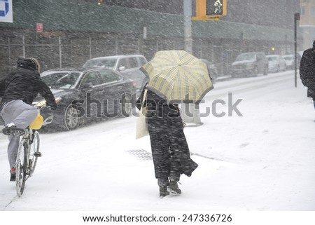 NEW YORK CITY - JANUARY 26 2015: Brooklyn Heights residents gird themselves in preparation for winter storm, Juno, the first major blizzard of 2015. Fighting winds on Henry Street - stock photo