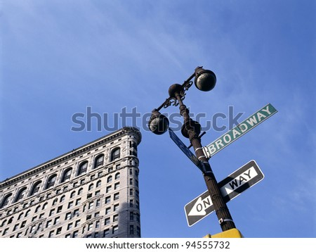 NEW YORK CITY - JULY 7: Flat Iron building is considered to be one of the first skyscrapers ever built. With Broadway street sign at foreground.July 7, 2009  Manhattan, New York City. - stock photo