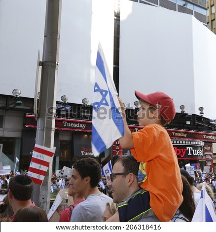 NEW YORK CITY - JULY 20 2014: Several thousand attended a rally in Times Square to support Israel's recent actions in Gaza. Little boy on father's shoulders carrying Israeli flag