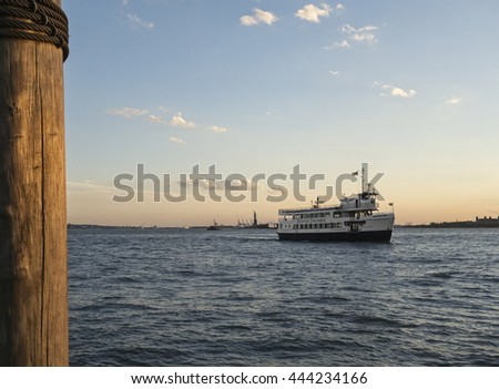 NEW YORK CITY - June 2016 - A Statue of Liberty ferry boat cruises by the Statue of Liberty at dusk - Manhattan, New York - June 22, 2016 - stock photo