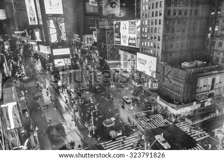 NEW YORK CITY - JUNE 13, 2013: Black and white view of tourists in Times Square at night. Times Square is a major commercial intersection and neighborhood in Midtown Manhattan. - stock photo