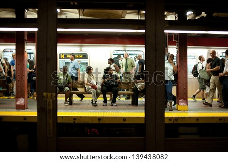 NEW YORK CITY - JUNE 28: Commuters waiting on platform on June 28, 2012 in NYC. The NYC Subway is one of the oldest and most extensive public transportation systems in the world, with 468 stations. - stock photo