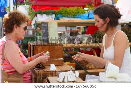NEW YORK CITY - JUNE 30 2012: Female shopper makes transaction at the Union Square Greenmarket, one of New York City's largest & best established direct markets for producers - stock photo