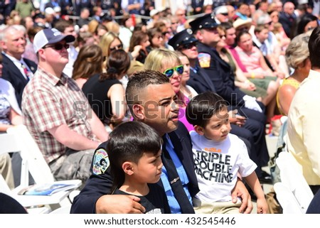 NEW YORK CITY - JUNE 1 2016: Mayor de Blasio & Commissioner Daniel Nigro presided over FDNY medal day on the steps of city hall. Firefighter watches ceremony with kids