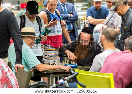 NEW YORK CITY - JUNE 17: People playing chess in bryant park. The Chess Area provides the public with an opportunity to play chess and backgammon for free. June 17, 2015 in Manhattan, New York City. - stock photo