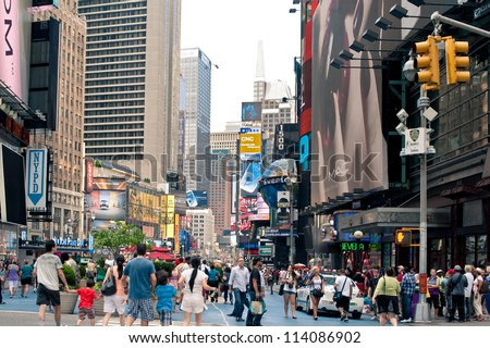 NEW YORK CITY - JUNE 28: People walking in Times Square, a busy tourist intersection of commerce Advertisements and a famous street of New York City and US, seen on June 28, 2012 in New York, NY. - stock photo