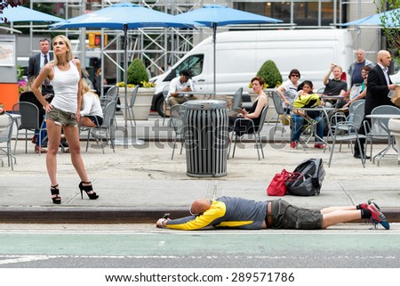 NEW YORK CITY - JUNE 16, 2015: strange kind of shooting on the street with mobile phone - stock photo