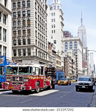 NEW YORK CITY - JUNE 28, 2014: Streets of NYC mid afternoon with FDNY firetruck and taxi cab in view and the Empire State Building. - stock photo