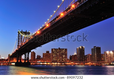 New York City Manhattan Bridge over East River at dusk illuminated with light with reflections and downtown skyline viewed from Brooklyn. - stock photo
