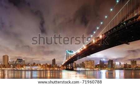 New York City Manhattan Bridge with city skyline at night illuminated over Hudson River. - stock photo