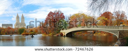 New York City Manhattan Central Park panorama at Autumn with skyscrapers, foliage, lake and Bow Bridge. - stock photo