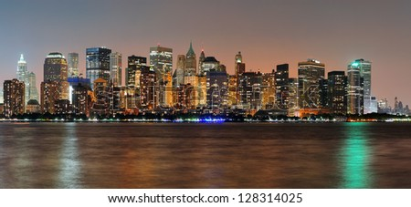 New York City Manhattan downtown skyline at dusk with skyscrapers illuminated over Hudson River panorama