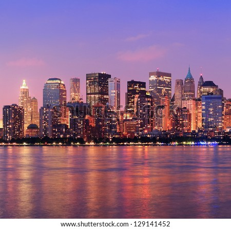 New York City Manhattan downtown skyline at dusk with skyscrapers illuminated over Hudson River panorama - stock photo