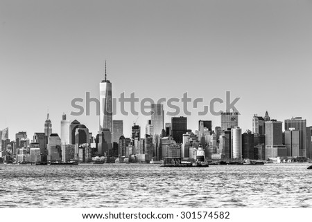 New York City Manhattan downtown skyline at dusk with skyscrapers illuminated over Hudson River panorama. Horizontal composition, copy space. Black and white image.