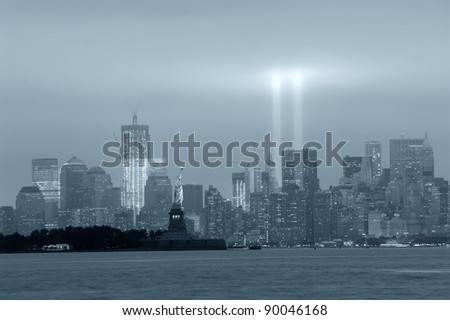 New York City Manhattan downtown skyline black and white at night with statue of liberty and light beams in memory of September 11 viewed from New Jersey waterfront. - stock photo