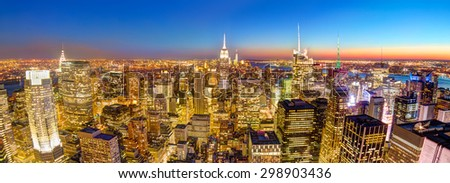 New York City. Manhattan downtown skyline with illuminated Empire State Building and skyscrapers at dusk seen from observation deck. Horisontal panoramic composition. - stock photo