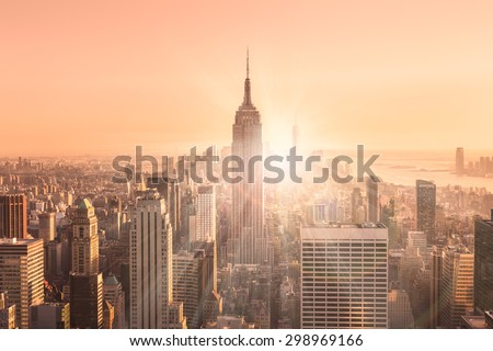 New York City. Manhattan downtown skyline with illuminated Empire State Building and skyscrapers at sunset. Vertical composition. Warm evening colors. Sunbeams and lens flare. - stock photo