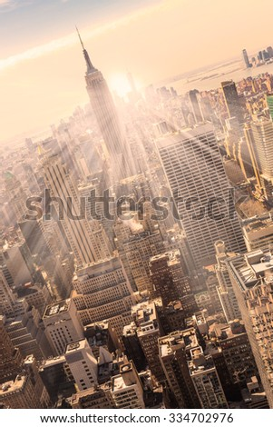 New York City. Manhattan downtown skyline with illuminated Empire State Building and skyscrapers at sunset. Vertical composition. Warm evening colors.  - stock photo