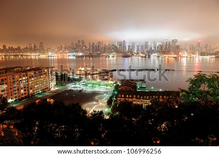 New York City Manhattan midtown skyline at night with skyscrapers over Hudson River viewed from New Jersey. - stock photo