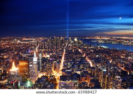New York City Manhattan panorama view at night with office building skyscrapers skyline illuminated over Hudson River and two light beam in memory of September 11. - stock photo