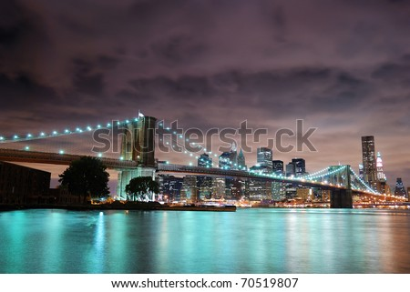 New York City Manhattan panorama view with Brooklyn Bridge at night with office building skyscrapers skyline illuminated over Hudson Rive