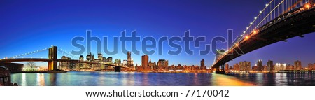 New York City Manhattan skyline panorama with Brooklyn Bridge and Manhattan Bridge over East River at dusk illuminated with reflections and downtown skyscrapers viewed from Brooklyn. - stock photo