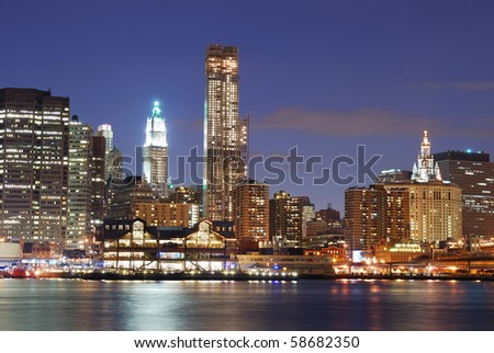 New York City Manhattan skyline with office skyscrapers building in at dusk illuminated with lights at night over Hudson River - stock photo
