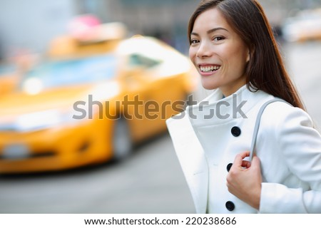 New York City Manhattan woman walking in street wearing coat downtown with yellow taxi cabs in background. Multiracial young urban professional in USA. - stock photo