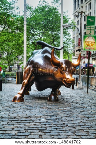 """NEW YORK CITY - MAY 12: Charging Bull sculpture on May 12, 2013 in New York City. The sculpture is a popular tourist destination, as well as """"one of the most iconic images of New York"""". - stock photo"""