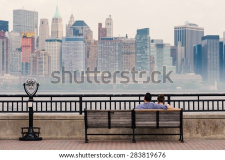 NEW YORK CITY - MAY, 2015: Couple relaxing in front of Manhattan skyline viewed from New Jersey Liberty State Park at daytime. - stock photo