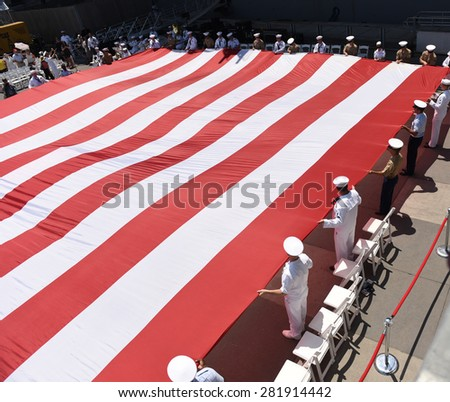 NEW YORK CITY - 25 MAY 2015: Mayor Bill de Blasio & Gen John Kelly presided over Memorial Day observances on Pier 86 by the USS Intrepid. Unfurling massive US flag on pier 86 - stock photo