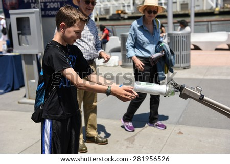 NEW YORK CITY - 25 MAY 2015: Mayor Bill de Blasio & Gen John Kelly presided over Memorial Day observances on Pier 86 by the USS Intrepid. Kids confront US Navy robotic arm on pier 86 - stock photo