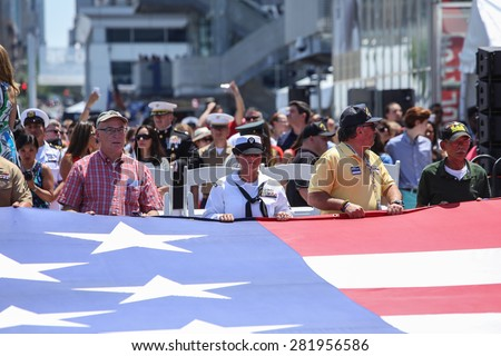NEW YORK CITY - 25 MAY 2015: Mayor Bill de Blasio & Gen John Kelly presided over Memorial Day observances on Pier 86 by the USS Intrepid. Unfurling enormous US flag on Pier 86 - stock photo