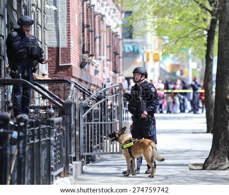 NEW YORK CITY - MAY 1 2015: NYPD emergency services, K9 & helicopter patrol search a closed off a block in Sunset Park, Brooklyn, for a robbery suspect. K9 unit outside apartment