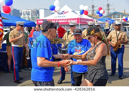 NEW YORK CITY - MAY 25 2016: Ships of the US Navy docked in the Brooklyn Ferry Terminal as the 28th annual Fleet Week started. WWii veteran Carl Tringali dances with BBQ Brethren's Sharon Silver
