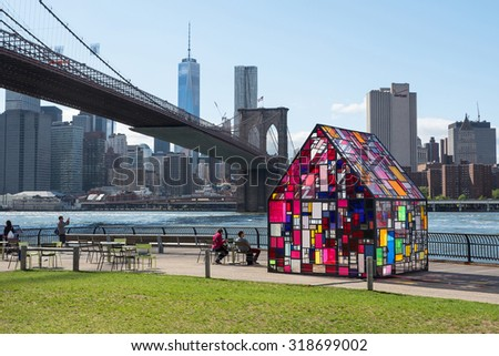 NEW YORK CITY - MAY 13, 2015: Stained glass sculpture by Tom Fruin under Brooklyn Bridge. Sculptor Tom Fruin installed his famous plexiglass house, Kolonihavehus, in Brooklyn Dumbo Park. - stock photo