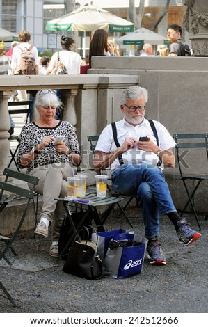 NEW YORK CITY, NEW YORK - MAY 1, 2014: Middle-aged tourist couple check their cellphones in Bryant Park, location of the NY Public Library. Seniors increasingly use technology to plan their travel.