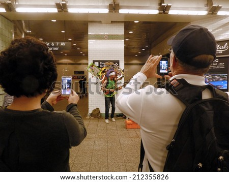 NEW YORK CITY, NEW YORK - MAY 1: Tourists take photos of a busker in the Times Square subway station. Street performers of all kinds make New York fascinating for visitors from all over the world.