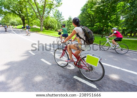 NEW YORK CITY, NEW YORK, USA - JUNE 14, 2014: Cyclists and joggers on Central Park East Drive on June 14, 2014. Central Park is a haven for the active lifestyle during the summer season. - stock photo