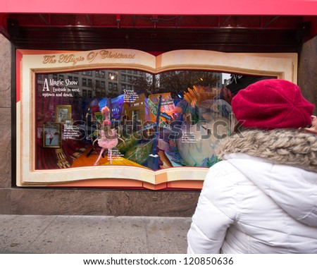NEW YORK CITY - NOV 30: Girl views holiday window display at Macy's Herald Square in NYC on Nov 30 2012. Since the early 1870's Macy'Â?Â?s has been stunning visitors with holiday window displays - stock photo