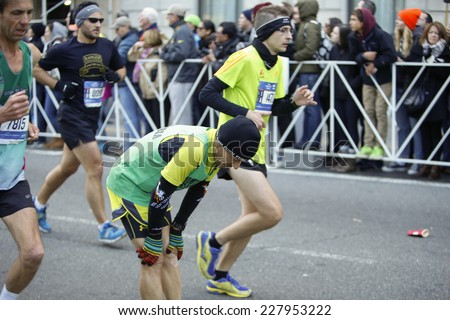 NEW YORK CITY - NOVEMBER 2 2014: the 43rd annual New York City Marathon saw more than 50,000 entrants run through all five boroughs. Male runner pausing with exhaustion only a few yards from finish - stock photo