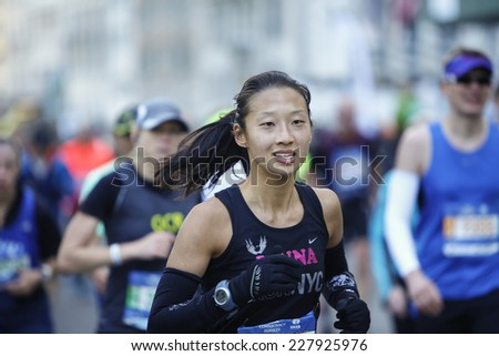 NEW YORK CITY - NOVEMBER 2 2014: the 43rd annual NYC Marathon saw more than 50,000 entrants race through all five boroughs. Young female competitor on 59th Street - stock photo