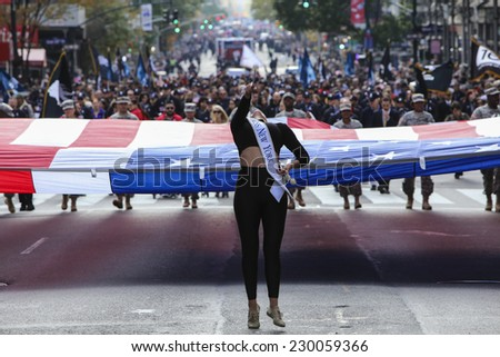 NEW YORK CITY - NOVEMBER 11 2014: the 95th annual Veteran's Day parade along Fifth Avenue is the largest Nov 11 celebration in the United States. Miss New York hurls baton in front of oversize US flag - stock photo